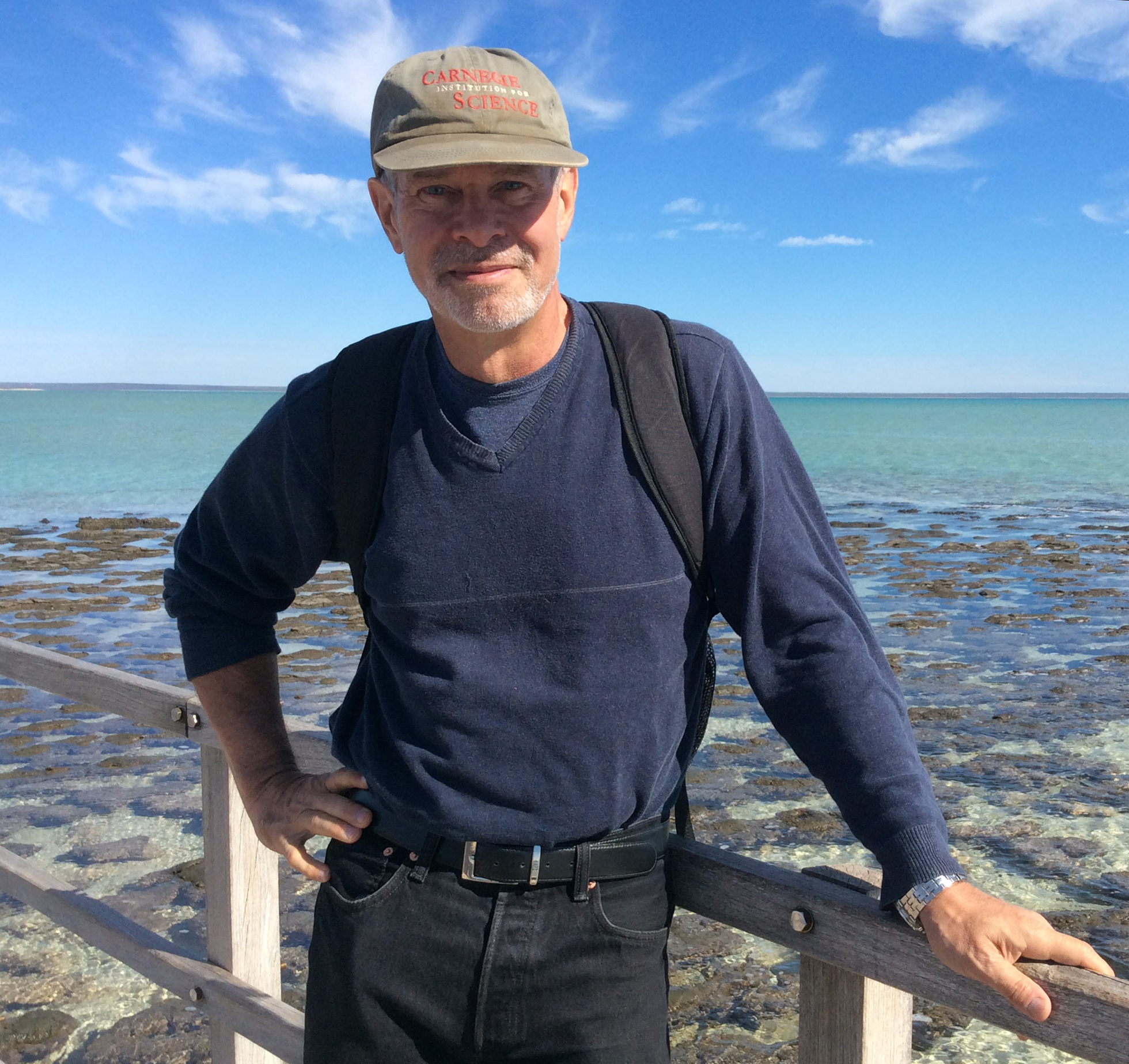 Bob Hazen on a boardwalk in front of Shark Bay, Australia, a shallow turquoise bay with dark greenish-brown stromatolite mats poking above the water surface.